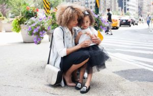 Mother embracing daughter on the sidewalk of New York City