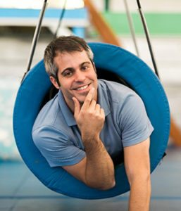 Occupational Therapist Andrew Klein inside a tunnel swing in the sensory gym
