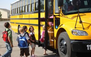 Back to School children lined up boring a school bus
