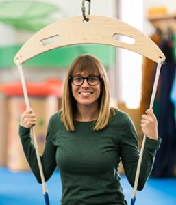 Clinical Director of Occupational Therapy, Occupational Therapist Katie Woolard seated on a frog swing in the sensory gym