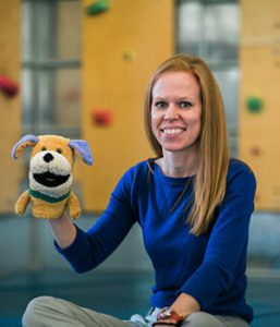 Speech Language Pathologist Kelly Jones with a dog puppet
