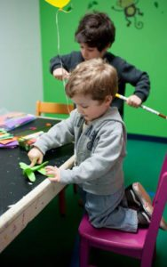 young boys participating in crafts at table for fine motor and visual motor development for occupational therapy