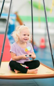 young girl sitting on a platform swing in the sensory gym for speech therapy