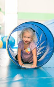 young girl crawling through tunnel in sensory gym