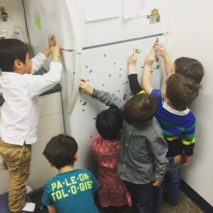 six children playing with magnetic on a refrigerator