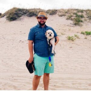 Front Desk Manger Dan at the beach with his dog