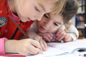 two young girls working on a pencil drawing