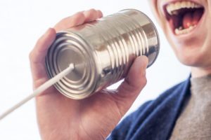 man yelling into a tin can indicating he is communicating