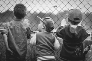 three boys watching a baseball game