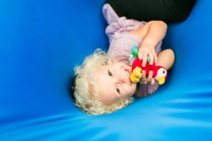 girl with bird toy in a swing, Sensory Integration - pediatric therapy durham