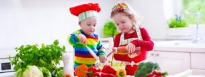 young girl and young boy making a salad
