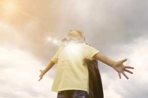 child with superhero cape looking up to sky