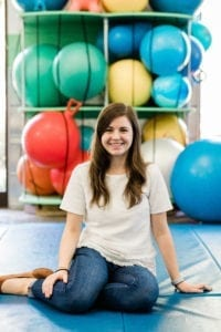 Speech Language Pathologist Laura sitting in sensory gym
