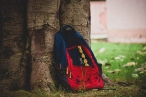 backpack resting on a tree