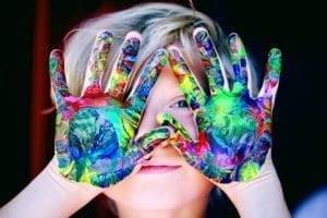 child with colorful, painted hands in front of face