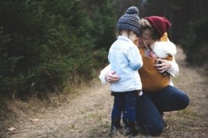 mother hugging daughter while holding infant baby on a walk