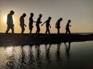 children silhouettes walking on beach