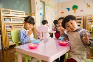 one girl and two boys eating at table together