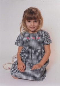 Speech Language Pathologist Taylor as a young girl, sitting in gingham fabric dress with three roses embroidered on the chest