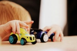 hands playing with blue and yellow car