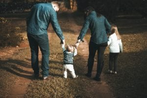 family of four, mom and dad walking while holding onto their infant son's hands while daughter walks a few steps ahead