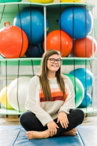 Community Engagement Coordinator Hailey sitting in front of therapy balls in the sensory gym