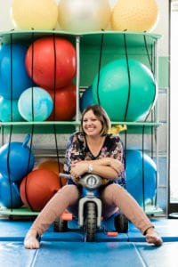 Occupational Therapist Nicole sitting on a tricycle in the sensory gym