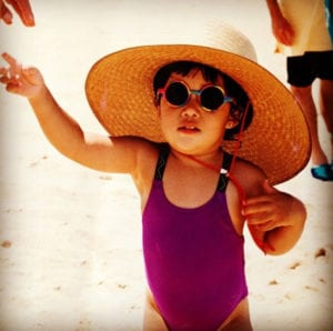 Speech Language Pathologist Amy as a toddler at the beach, with an oversized hat and round glasses
