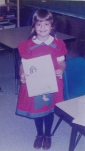 Occupational Therapist Nicole as a young girl, wearing a red dress showing her picture in a classroom