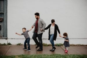 family of four walking in a straight line, with son leading his father, father leading wife, and wife leading her daughter