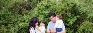 family of four, older son in mom's arms and infant son in dad's arms