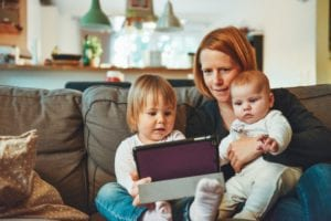 mom sitting on sofa with toddler daughter and infant daughter while looking at a tablet