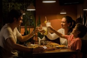 family of three toasting their glasses while eating at a pizza restaurant