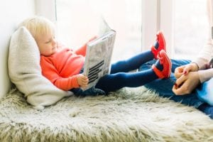 toddler girl reading a book while her feet are resting on her mother's knee