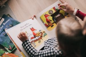 young child reading a book about a fox with his mom, while sitting on her lap