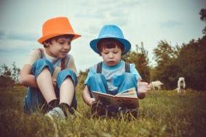 two siblings, one in a orange hat, and one in a blue hat reading a book together