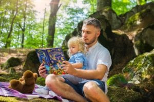 father reading a book to his daughter while picnicking in the woods