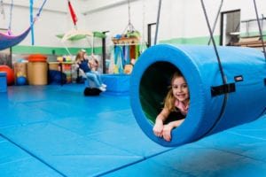 girl swinging inside a tunnel swing and another girl on the frog swing in the background in the sensory gym