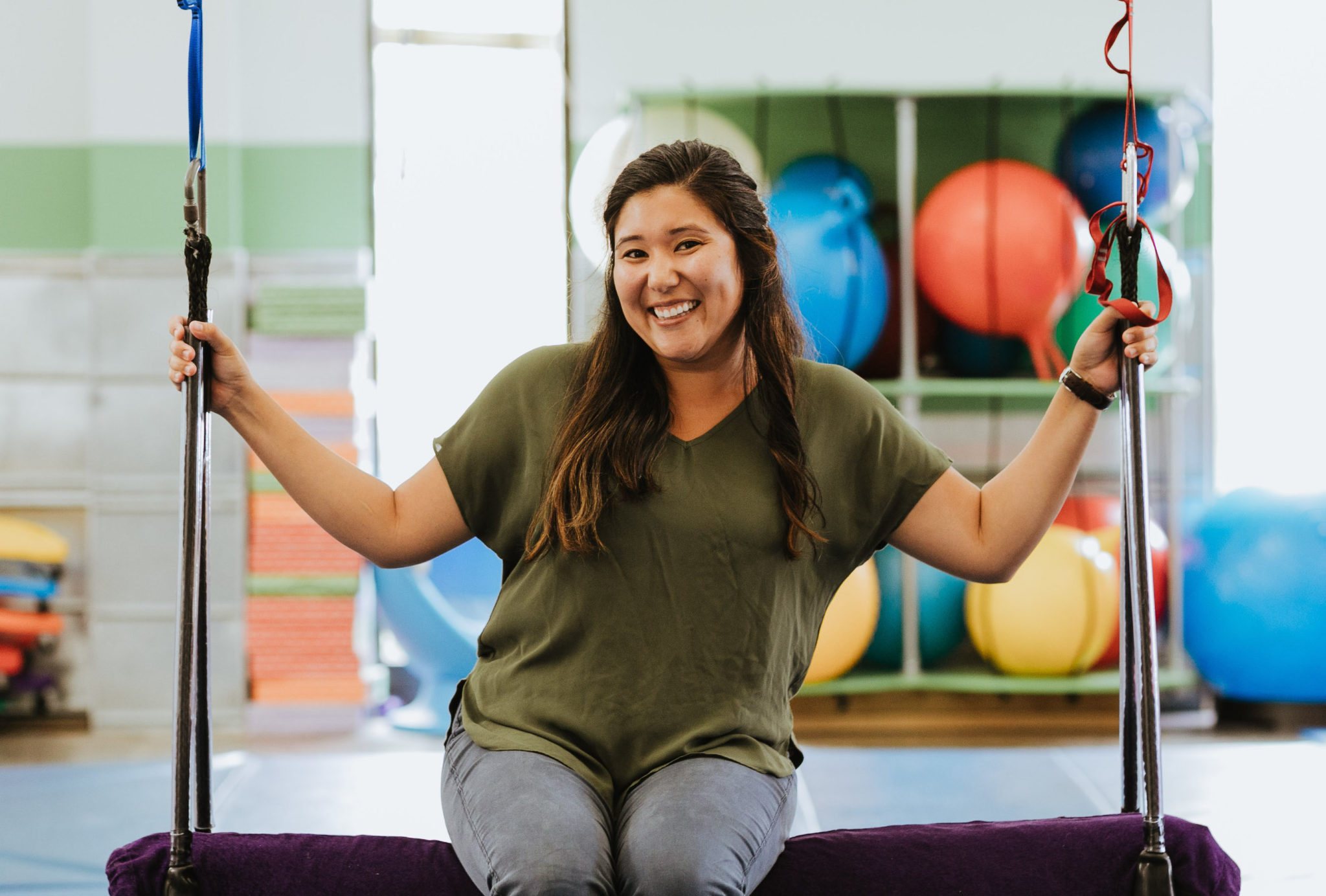Speech Language Pathologist Amy sitting on a swing in the sensory gym