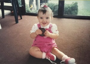 Occupational Therapist Jakelyn as a toddler, wearing pink overalls with a large cookie in her hands
