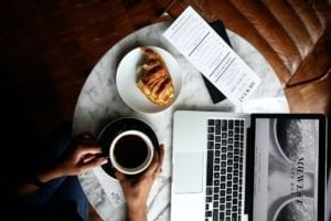 Macbook Pro with coffee and breakfast at a cafe