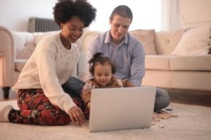 young family of three, sitting on the floor while using a laptop