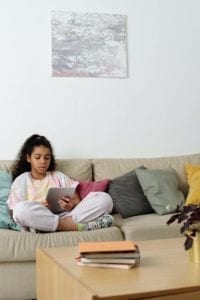 girl sitting on the sofa reading on her tablet