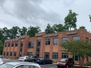 Two story brick building with large windows. Large white letters go across the top of the building announcing the names of the businesses inside, including Emerge Pediatric Therapy