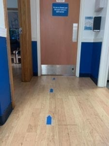 blue arrows on the floor leading to the gym entrance door