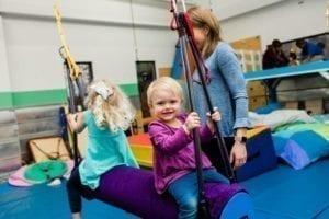 two girls swinging in a sensory gym as an occupational therapist stands by