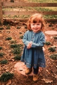Occupational Therapist Maddy as a little girl in a denim dress standing outside with a fence in the background
