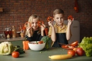girl and boy in a kitchen, holding up slices of red bell pepper