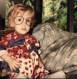 Occupational Therapist Miranda as an infant girl wearing large glasses and a red, white, and blue onesie sitting next to a blue pillow