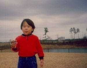 Occupational Therapist Taz as a young boy wearing red shirt and blue jeans eating a pie while walking close to a lake with dark clouds above